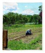 Woman Planting Garden Near Barn Fleece Blanket