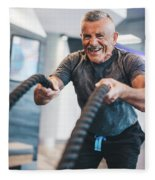 Senior Man Exercising With Ropes At The Gym. Fleece Blanket