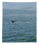 A Whale's Tail Above Water With Sail Boat In The Background Fleece Blanket