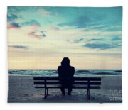 Man In Hood Sitting On A Lonely Bench On The Beach Fleece Blanket