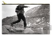 A Man Jumps From One Rock To Another Carry-all Pouch