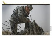 A Soldier Communicates Using A Carry-all Pouch