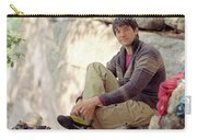 A Young Rock Climber Puts On A Climbing Carry-all Pouch