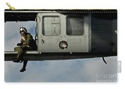 A U.s. Navy Naval Air Crewman Guides Carry-all Pouch