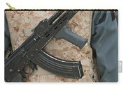 An Ak-47 Rests On The Sling Of An Carry-all Pouch