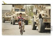 An Iraqi Boy Rides His Bike Past A U.s Carry-all Pouch by Stocktrek Images