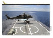 An Sh-60f Sea Hawk Helicopter Lowers Carry-all Pouch