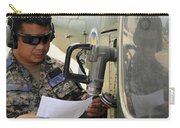 A Honduran Crew Chief Consults Carry-all Pouch