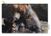 Adorable Grizzly Bear Playing With A Maple Leaf While Sitting In Carry-all Pouch