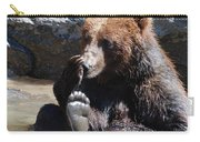 Grizzly Bear Licking His Paw While Seated In A Muddy River Carry-all Pouch