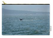 A Whale's Tail Above Water With Sail Boat In The Background Carry-all Pouch