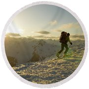 A Man Backcountry Skiing At Sunset Round Beach Towel