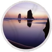 Needles Silhouetted Cannon Beach Oregon Round Beach Towel