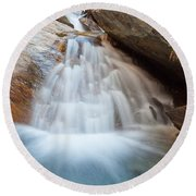Small Waterfall Casdcading Over Rocks In Blue Pond Round Beach Towel