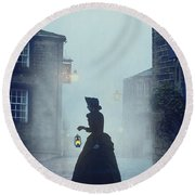 Victorian Woman With An Oil Lamp At Night On A Cobbled Street Round Beach Towel