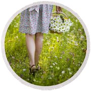 Woman Walking Through A Wild Flower Meadow With A Basket Of Flow Round Beach Towel