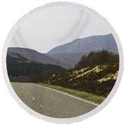 Highway Running Through The Wilderness Of The Scottish Highlands Round Beach Towel