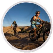 Couple Mountain Biking, Moab, Utah Round Beach Towel