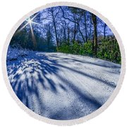 Snow Covered Road Leads Through The Wooded Forest Round Beach Towel