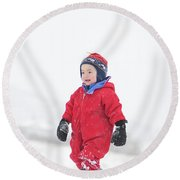 A Two Year Old Boy Plays In A Snowy Round Beach Towel