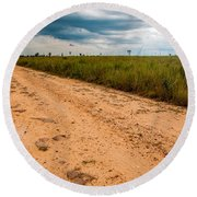 A Dirt Road In The Plains Round Beach Towel