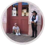 A Dog And A Re-enactor Rest In The Front Of The Bird Cage Theater Tombstone Arizona Round Beach Towel
