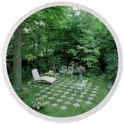 A Garden With Checkered Pavement Round Beach Towel