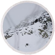 A Hiker Approaches A Snowy Peak Covered Round Beach Towel