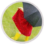 A Little Girl Walking In The Rain While Round Beach Towel