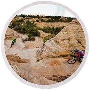 A Male And Female Mountain Biker Ride Round Beach Towel