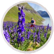 A Male Hiker In Sunny Flower Field Round Beach Towel