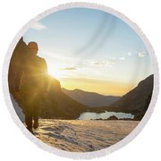 A Man Hiking On Snowfield At Sunrise Round Beach Towel