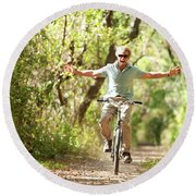 A Man Rides A Bicycle Round Beach Towel