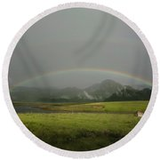 A Rainbow Over A Valley With A Small Round Beach Towel
