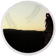 A Silhouette Of A Couple Rock Climbers Round Beach Towel