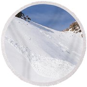 A Small Slab Avalanche With Two Guides Round Beach Towel
