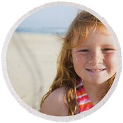 A Smiling Young Girl Enjoys A Sunny Round Beach Towel