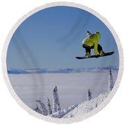 A Snowboarder Catches Air Off A Jump Round Beach Towel