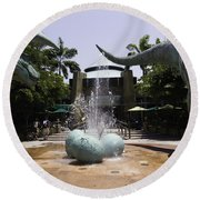 A Water Fountain With Dinosaur Eggs And Dinsosaurs In Universal Studios Round Beach Towel