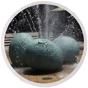 A Water Fountain With Dinosaur Eggs In The Universal Studios Singapore Round Beach Towel