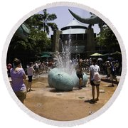 A Water Fountain With Dinosaur Eggs In Universal Studios Singapore Round Beach Towel