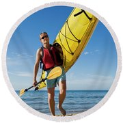 A Woman Carrying Her Sea Kayak Round Beach Towel