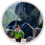 A Woman Hiking High In The Mountains Round Beach Towel