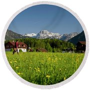 A Woman Walks Through An Alpine Meadow Round Beach Towel