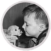 A Young Boy Is Face To Face With A Puppy Tongue. Round Beach Towel