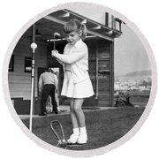 A Young Girl Hits A Golf Ball Round Beach Towel