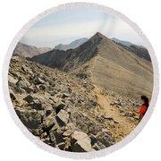A Young Woman Hikes Borah Peak Round Beach Towel