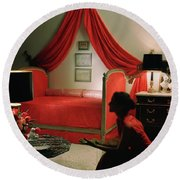 A Young Woman Sitting In A Red Bedroom Round Beach Towel