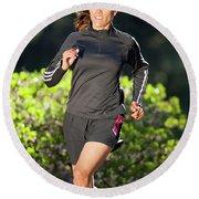 An Athletic Woman Trail Running Round Beach Towel