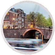 Canal Bridge And Boat Tour In Amsterdam At Evening Round Beach Towel